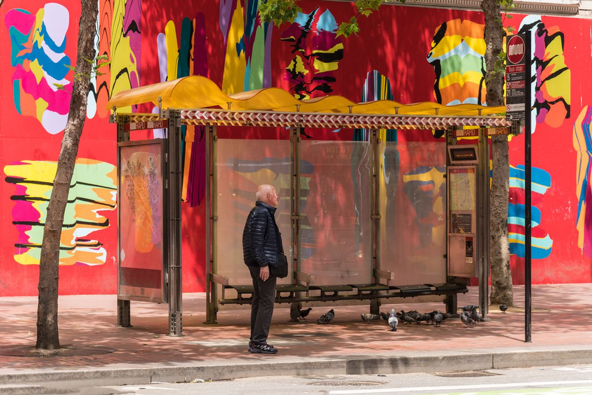 A man waiting at a Muni bus stop in front of a bright red mural.