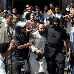 Egyptians security forces escort an Islamist supporter of the Muslim Brotherhood out of the al-Fatah mosque, after hundreds of Islamist protesters barricaded themselves inside the mosque overnight, following a day of fierce street battles that left scores of people dead, near Ramses Square in downtown Cairo, Egypt, Saturday, Aug. 17, 2013. Authorities say police in Cairo are negotiating with people barricaded in a mosque and promising them safe passage if they leave. Muslim Brotherhood supporters of Egypt's ousted Islamist president are vowing to defy a state of emergency with new protests today, adding to the tension.