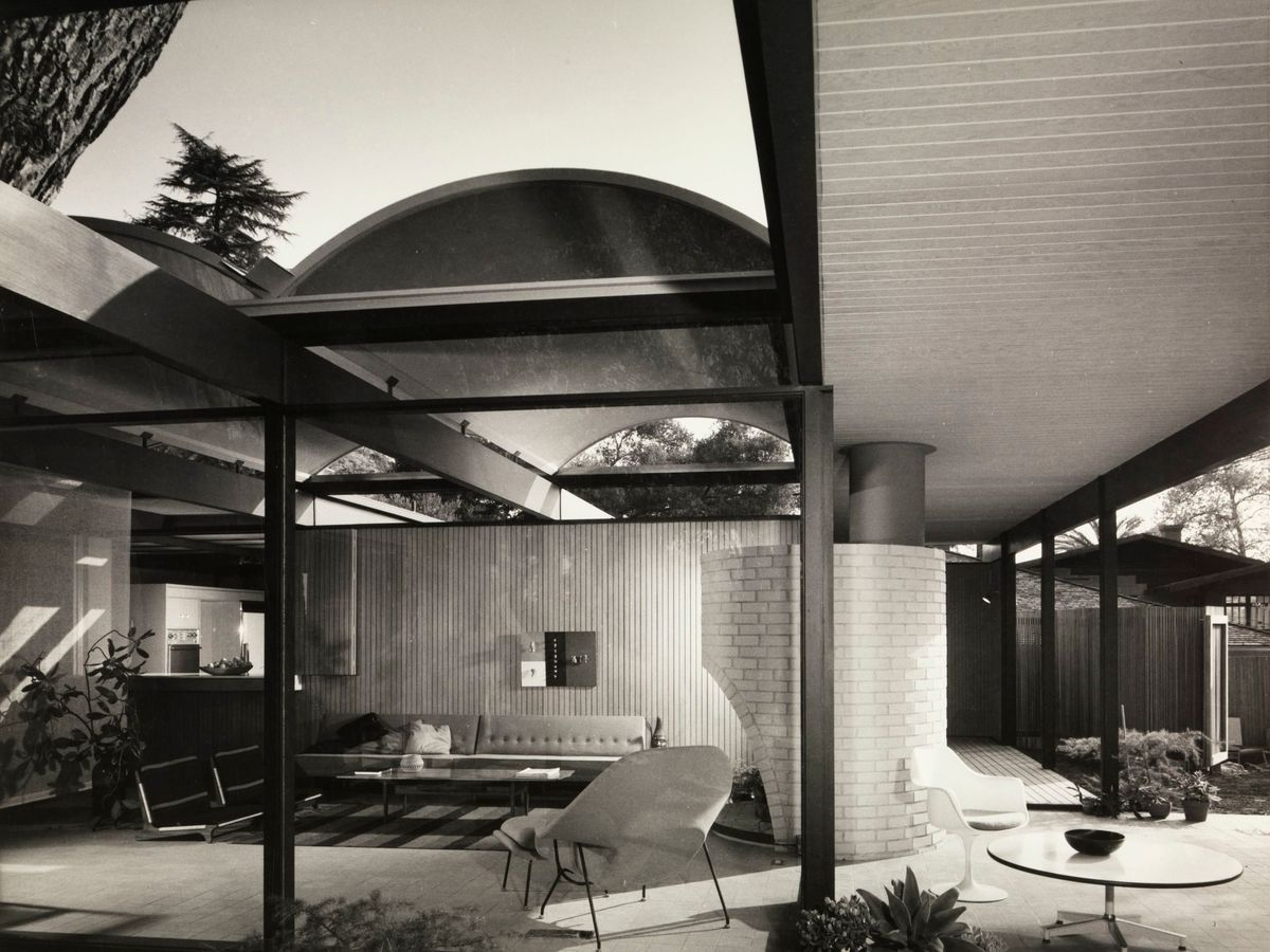 A house with glass walls and a canopy with an opening to let in sunlight
