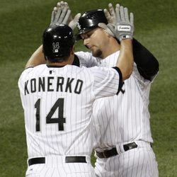 Chicago White Sox's Paul Konerko greets A.J. Pierzynski at home after they both scored on Pierzynski's two-run home run off Baltimore Orioles starting pitcher Tommy Hunter during the second inning of a baseball game, Wednesday, April 18, 2012, in Chicago.