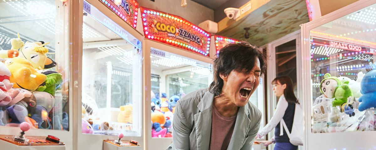 A Squid Game contestant screams, in front of a background of brightly colored claw vending machines