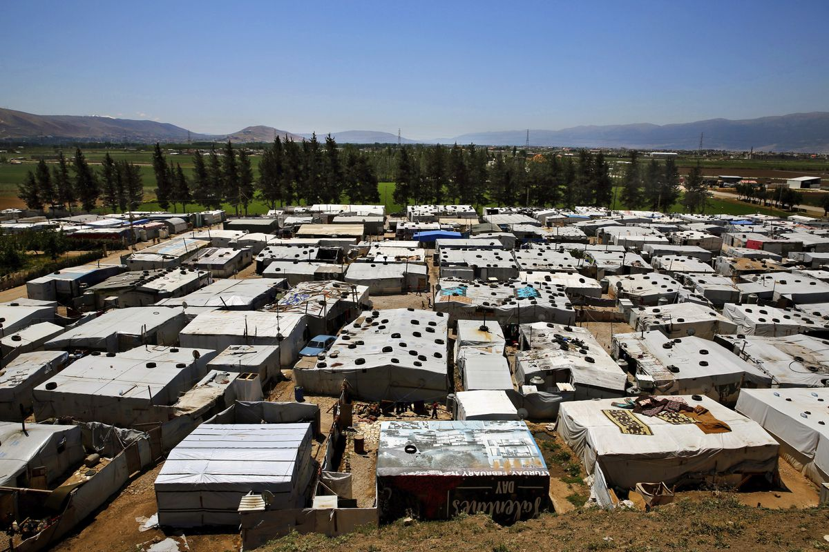 This Monday, April 23, 2018 photo, Syrian refugees walk outside their tents at a Syrian refugee camp in the town of Bar Elias, in Lebanon's Bekaa Valley. A leading international rights group and the U.N.'s refugee agency say Lebanese authorities have been