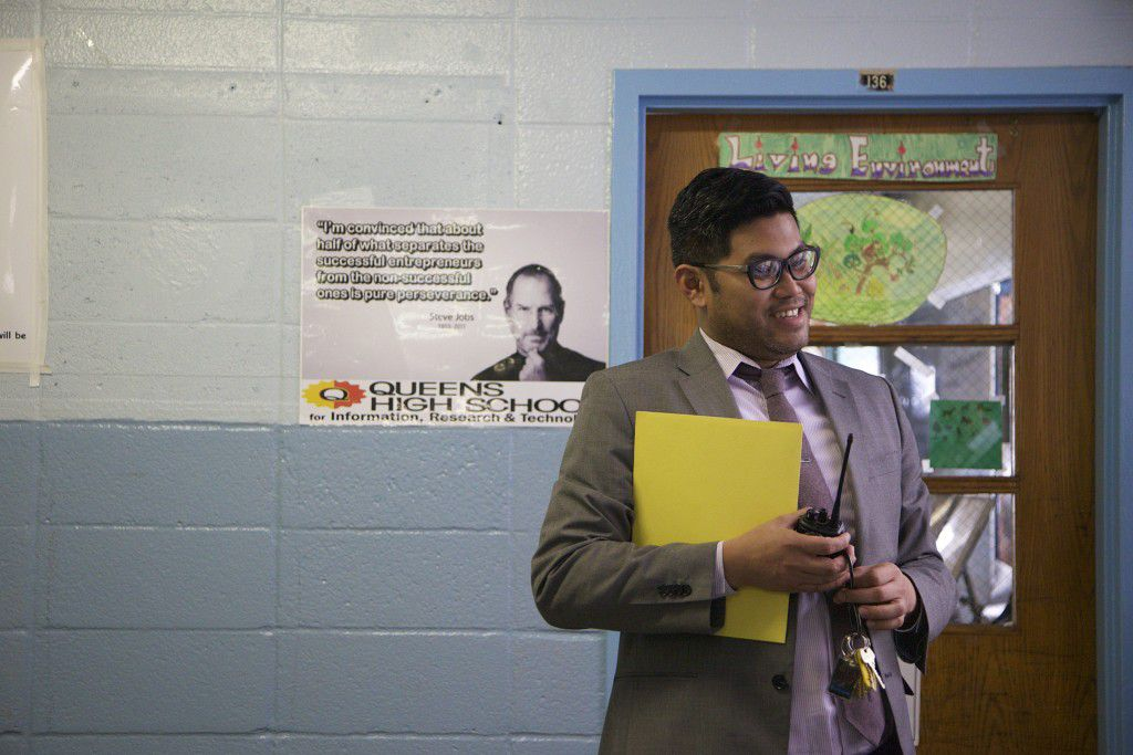 As a poster image of Steve Jobs looks on, Principal Carl Manalo speaks with a teacher in the hallway of QIRT.