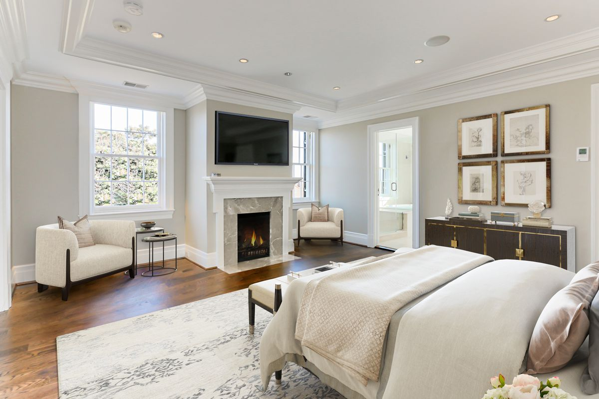 Bedroom outfitted in neutral colors and a TV above a fireplace.
