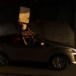 A vehicle with activists holding up pro Black Lives Matter signs drives on 60th Street, during a protest over the shooting of Jacob Blake, Tuesday, Aug. 25, 2020, in Kenosha, Wis.