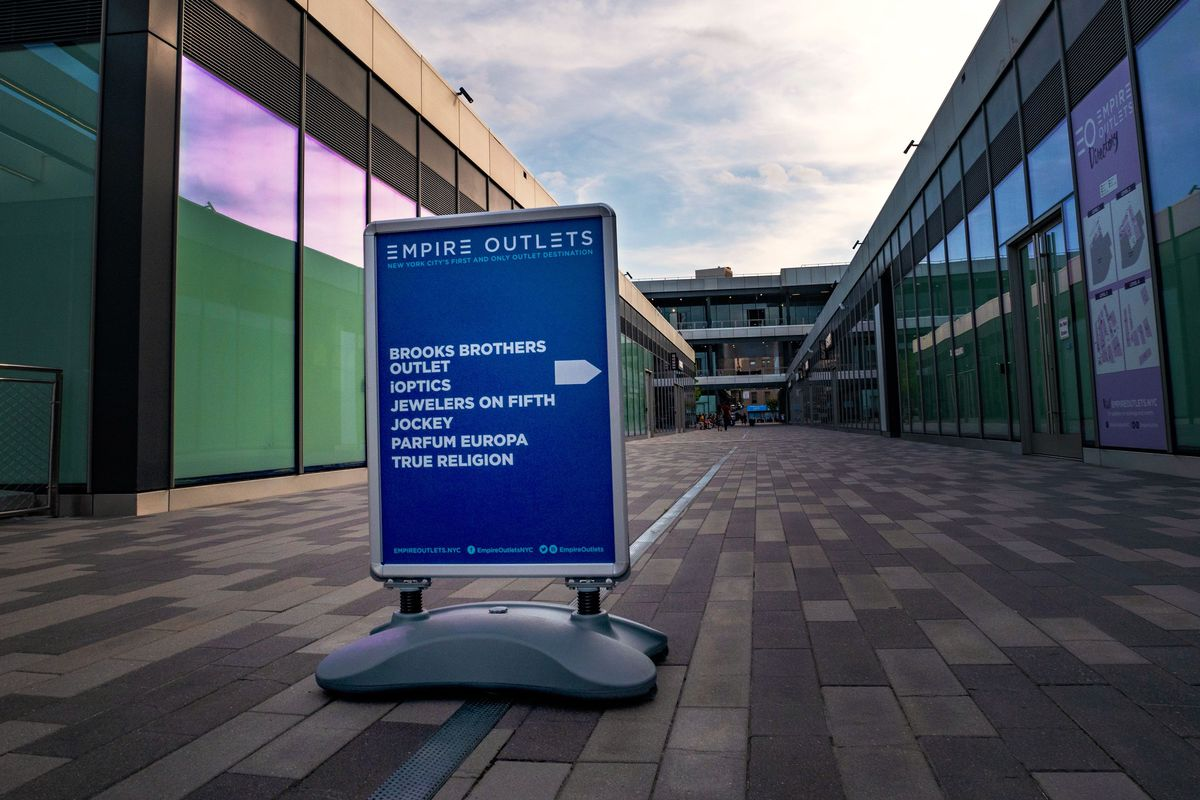 """A sign sits in the middle of an empty shopping mall. The sign reads """"Empire Outlets"""" and lists stores like Brooks Brothers, Jockey, True Religion, and iOptics."""