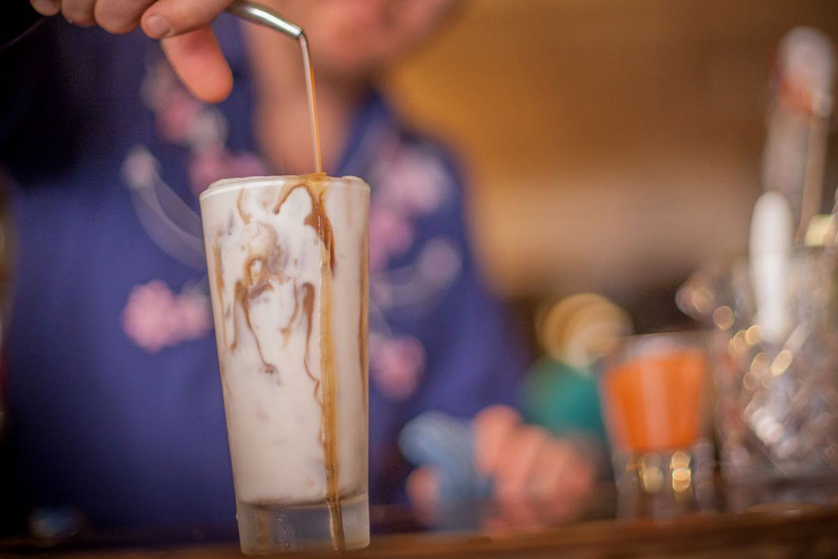 A bartender in a blue shirt pours liquid into an already overflowing highball glass, filled with a creamy-looking cocktail.
