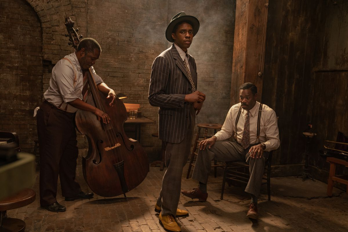 Three men stand in a room, one holding an upright bass.