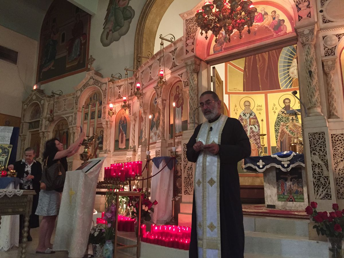 Rev. Nick Jonas talks to parishioners and visitors Monday at Holy Trinity Hellenic Orthodox Church on the Northwest Side.