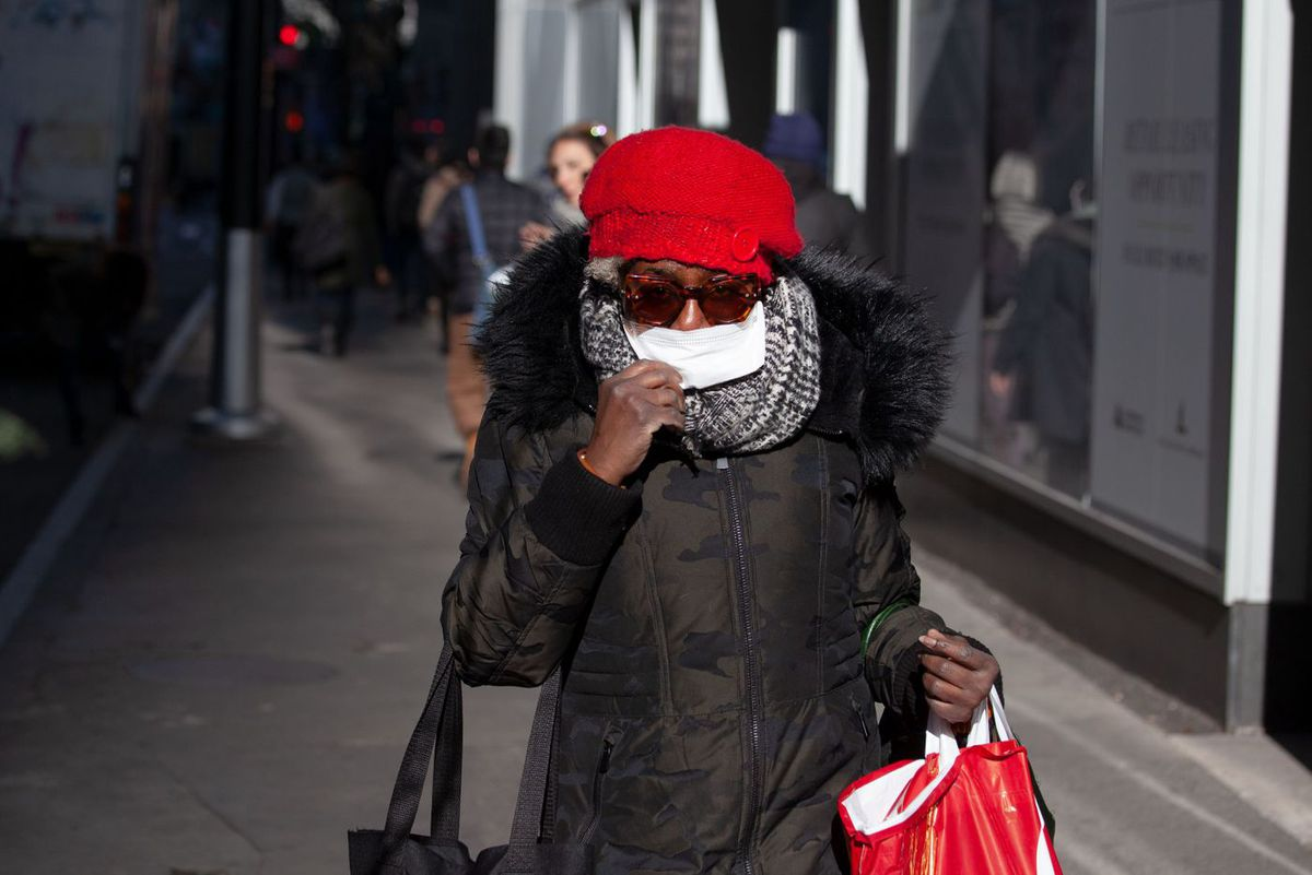 A pedestrian in lower Manhattan wears a surgical mask during the morning commute.