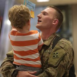 Ander Wilson shows his uncle Sgt. Bradin Wilson a book at the Salt Lake International Airport in Salt Lake City on Tuesday, Aug. 27, 2019, as Sgt. Wilson and other members of the Utah National Guard's 4th Infantry Division Main Command Post Operational Detachment return home after serving in Afghanistan for 10 months in support of Operation Freedom's Sentinel.