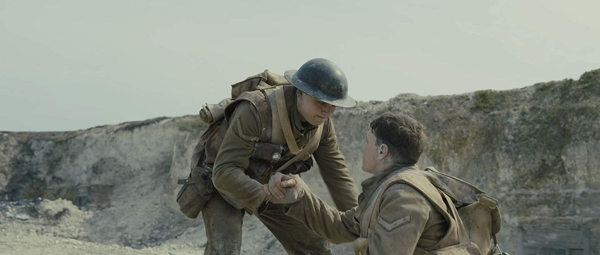 a young soldier lifts his friend off the ground of a salty earth trench