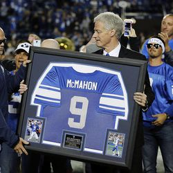 Former BYU player Jim McMahon receives a jersey from BYU President Kevin J Worthen as he is honored at Brigham Young University in Provo, Friday, Oct. 3, 2014.