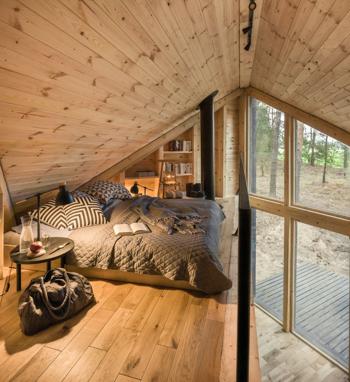 Bed tucked into lofted corner.