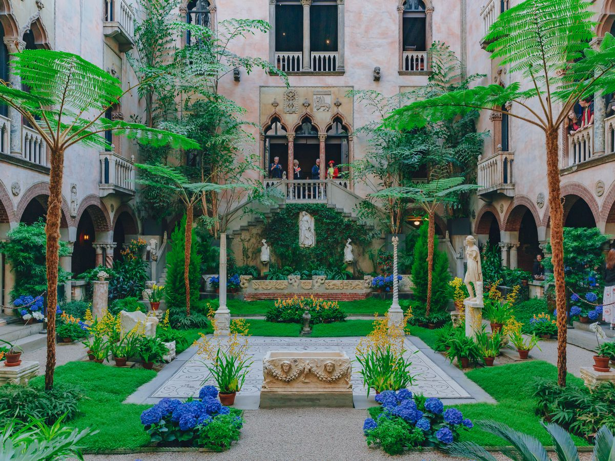 A lush and well-organized interior courtyard with lots of plants and grass.