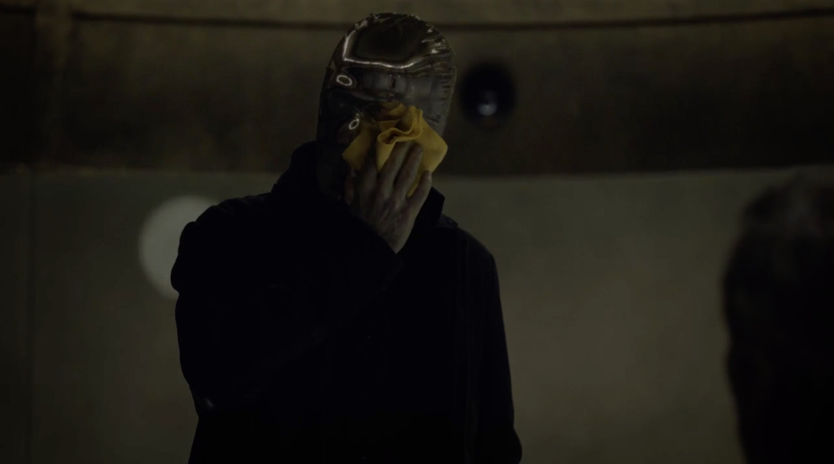 Looking Glass (Nelson) wipes his mask.