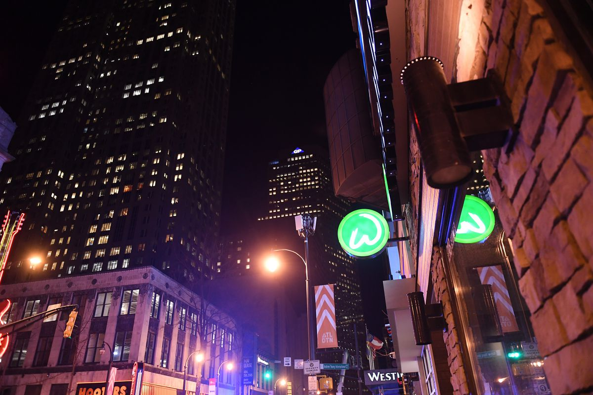 The exterior green logo for Wahlburgers on Peachtree Street looking toward downtown Atlanta