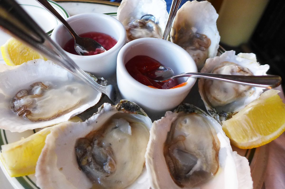 A plate with six raw oysters, two sauces, and lemon wedges.