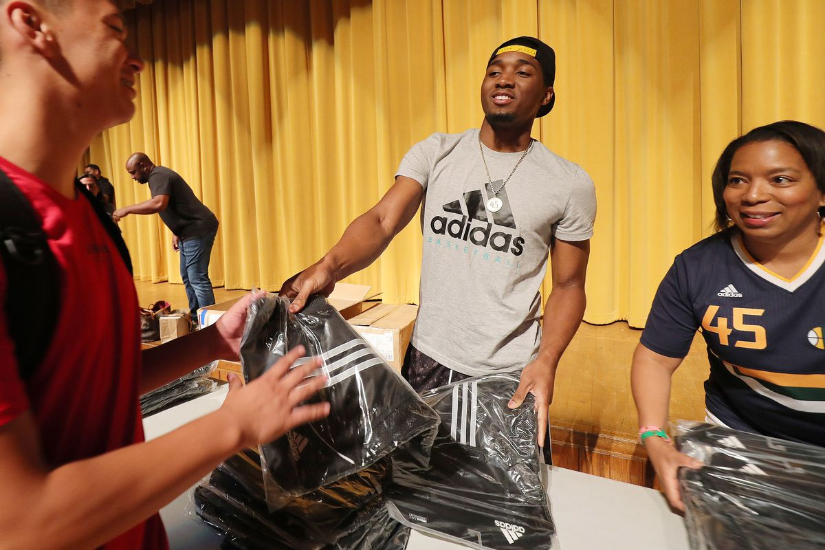 Utah Jazz player Donovan Mitchell and his mother Nicole Mitchell hand out backpacks to Kearns High students in Kearns on Tuesday, Aug. 21, 2018.