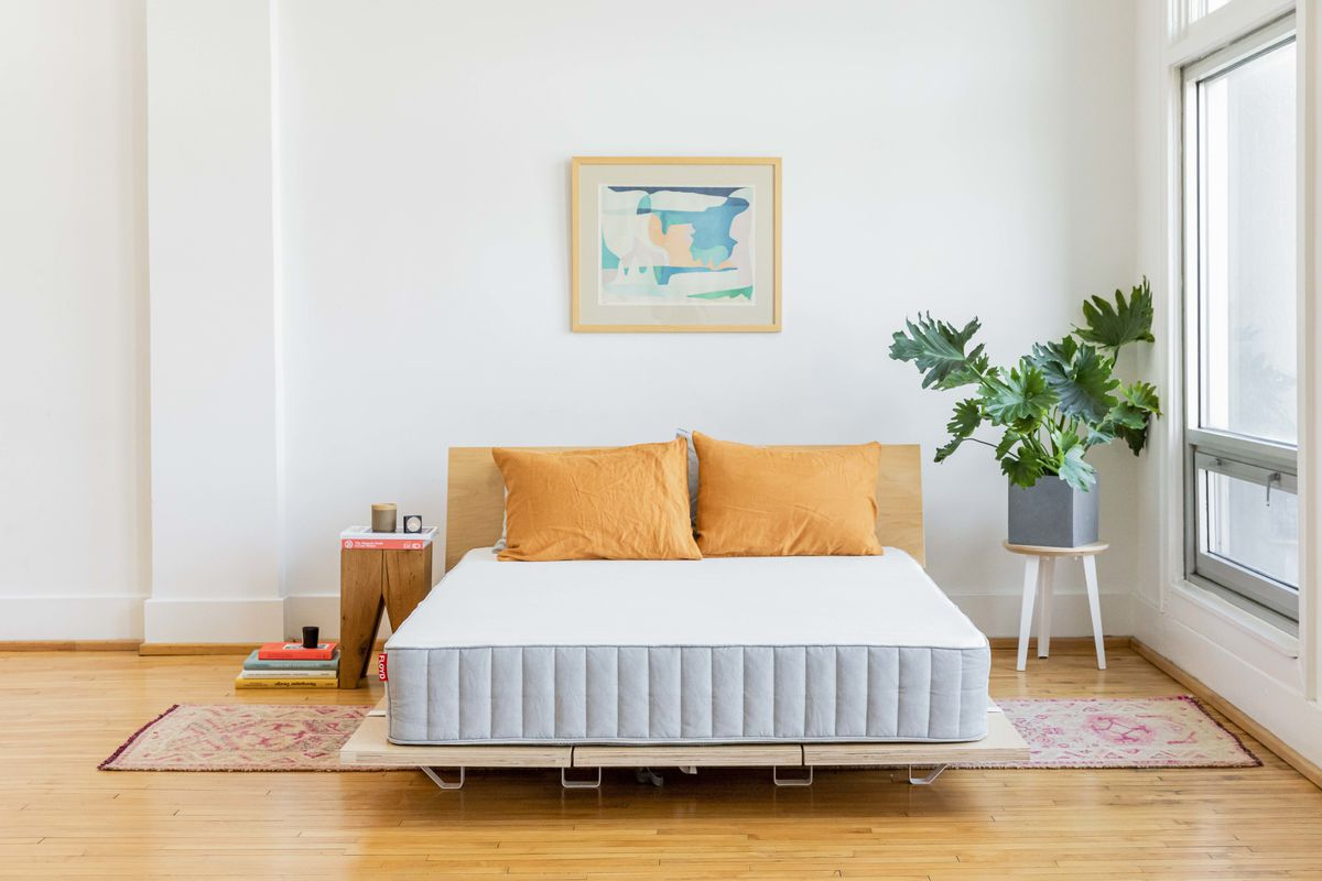 Mattress on wooden bed frame, with two orange pillows.