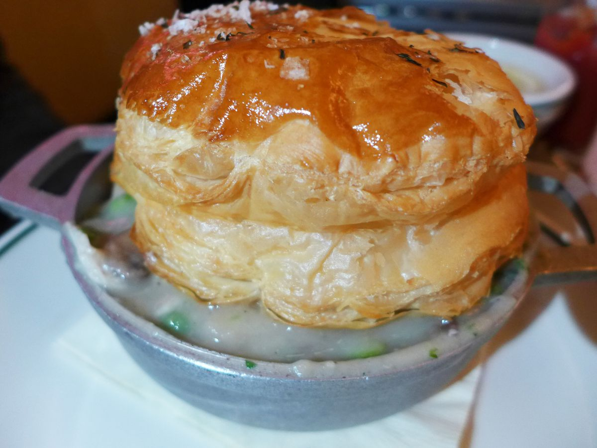 A pie in a pot with a big puffy pastry on top.
