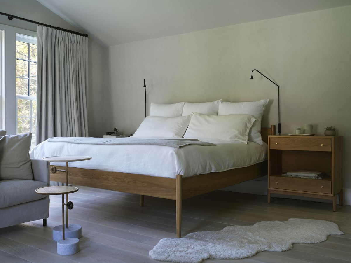A wooden platform bed with white bedding.