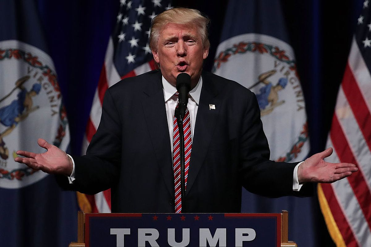 Former President Donald Trump stands, in a navy suit and red tie, hands spread wide, speaking into a microphone at a podium with his name on it and American flags behind him.