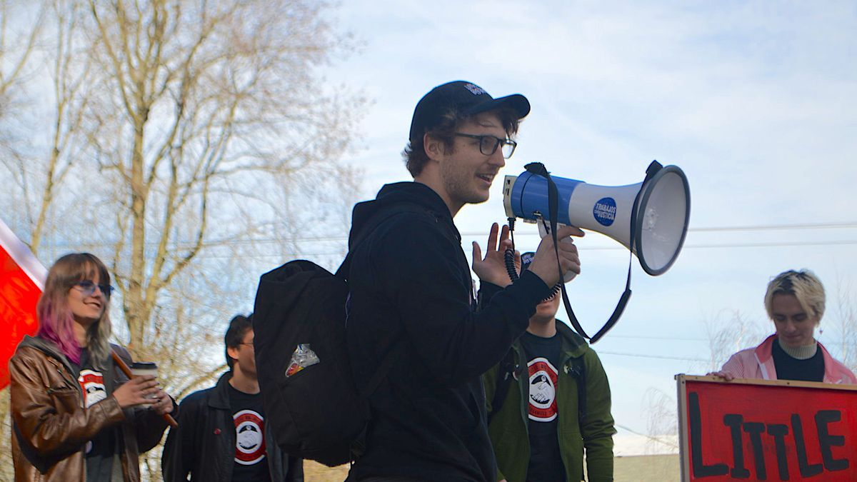 Cameron Crowell holds a megaphone while standing with four other employees of Little Big Union. One person holds a sign. Cameron is dressed in all black, with a cap and glasses.