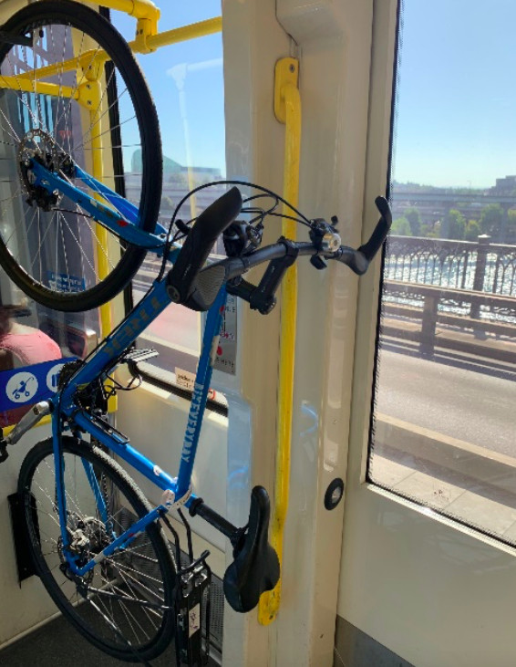 A bright blue bike is seen hanging on a yellow bike rack inside a light-rail train car as the train travels on a wide bridge over a river.