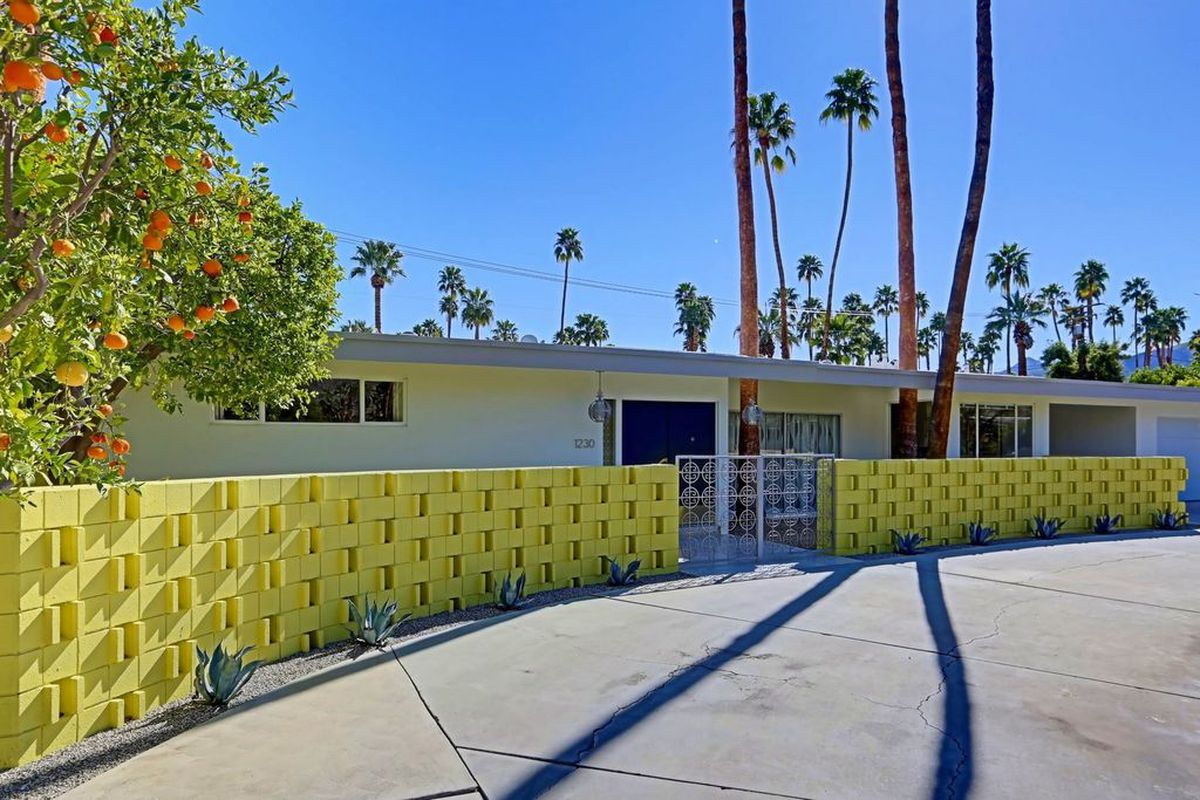 Exterior shot of low-slung midcentury-style home with flat roof and low yellow brick wall enclosing the front. A bright blue door makes the front entrance. Palm trees all around.