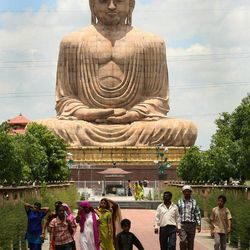 Tourists and devotees walk at the 80-foot Buddha statue at Bodhgaya, India, in this July 5, 2006, file photo.