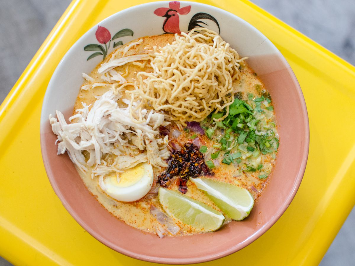 Overhead shot of a bowl of khao soi on a bright yellow surface. The bowl itself has a traditional Thai pattern on it, including a rooster design. The khao soi includes pickled mustard greens, an egg, lime wedges, a nest of crispy noodles, and more.
