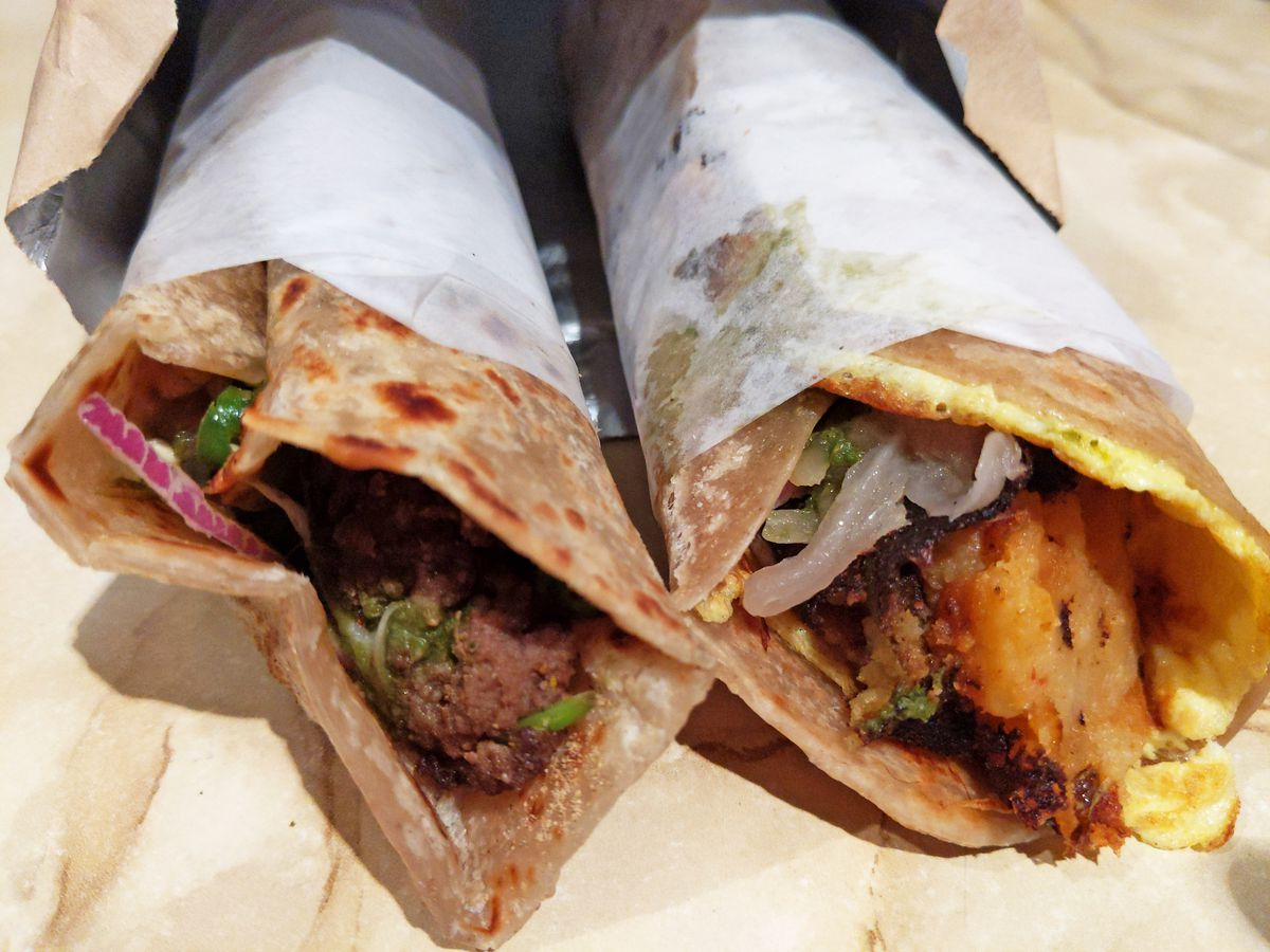 A pair of rolled flatbreads in wrapped in tissue with fillings sticking out the ends.