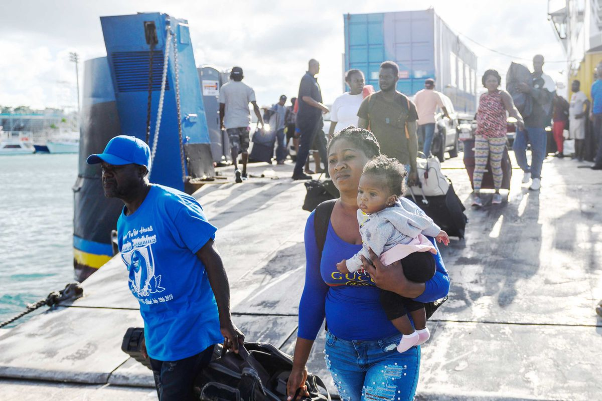 A woman holding a baby girl walks off a ferry with a crowd of other people carrying suitcases.