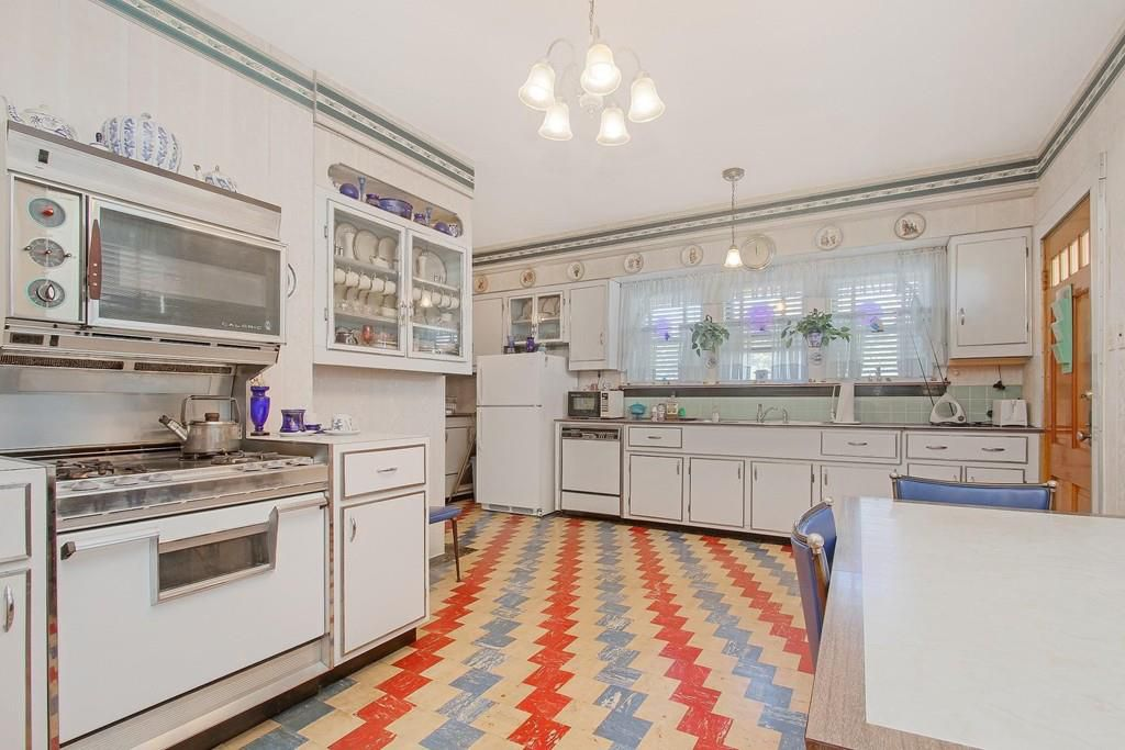 A large kitchen with older counters and a striking diagonal tile pattern on the floor.