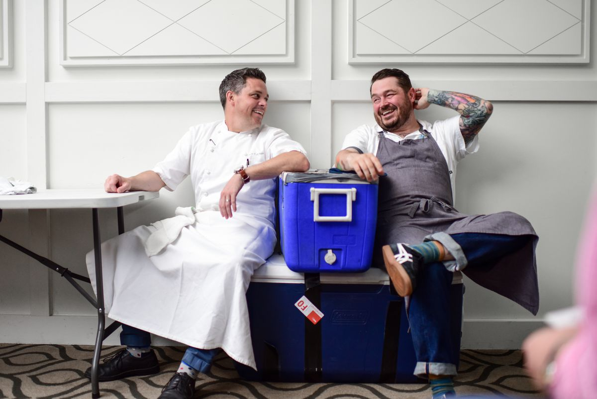 Sean Brock and Gavin Kaysen sit on coolers, looking at each other and laughing