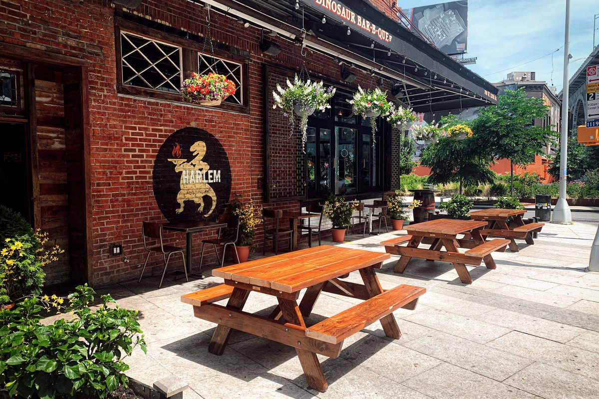 The exterior of a restaurant with several brown tables and benches placed out front