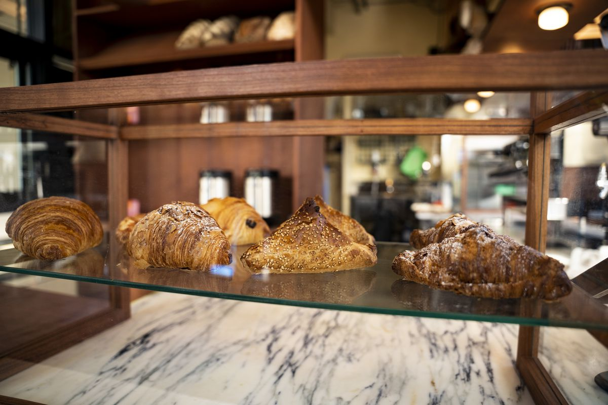 A display case is filled with handmade pastries, including croissants and bureka