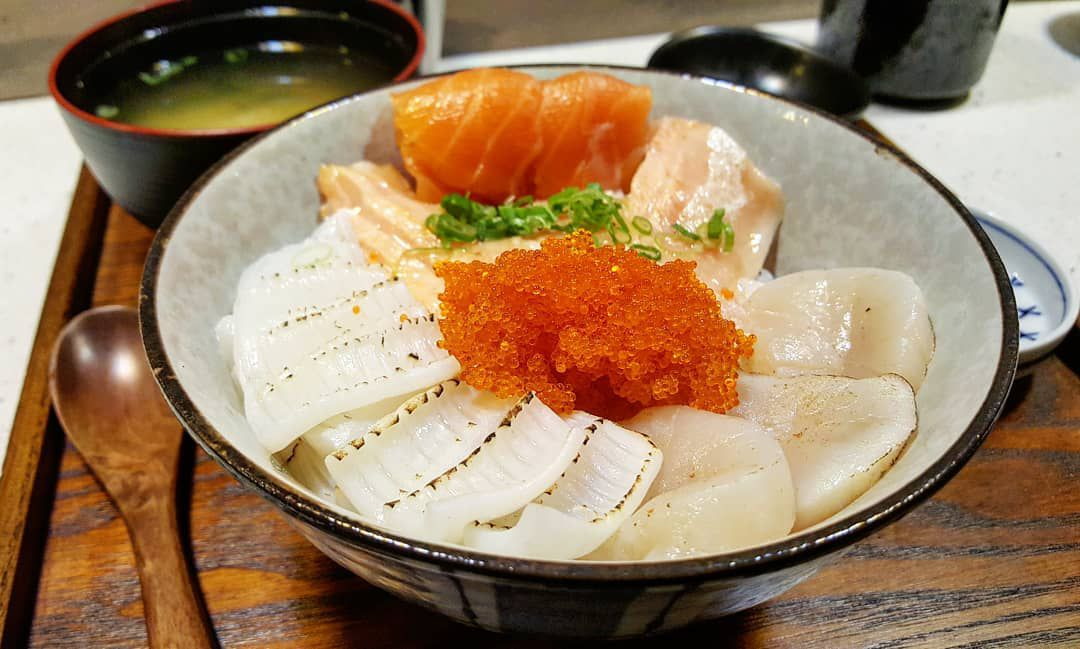 A bowl of raw seafood, including salmon and salmon roe, on rice, served on a wooden tray with miso soup