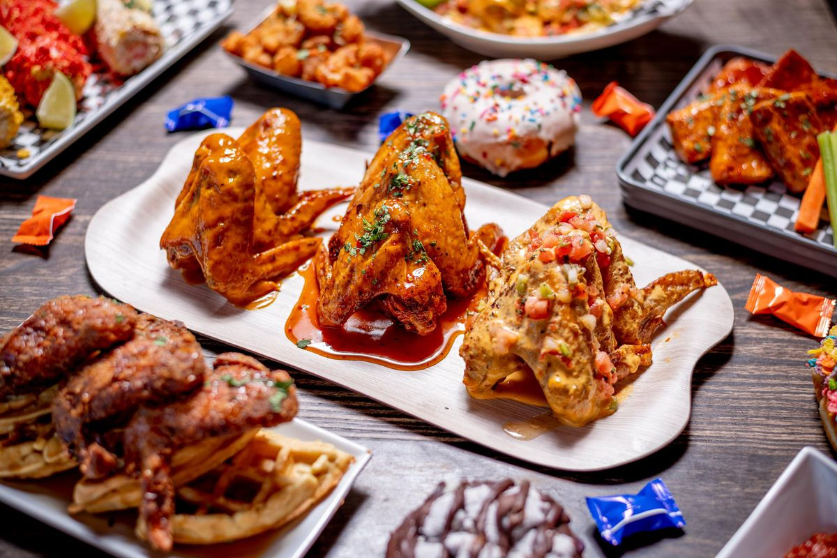 Several containers are overflowing with wings piled up and covered with different sauces. A doughnut sits in the middle of the table, a nod to the location inside Glam Doll Donuts Northeast location where B.A.D. Wingz will open