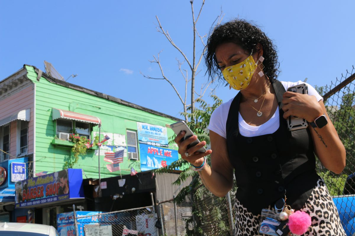 A woman in a yellow mask looks at her phone, with a green building behind her.