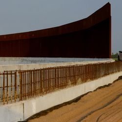A Border Patrol agent drives along the border wall near McAllen, Texas, on Tuesday, June 22, 2021. Large gaps can be seen along the unfinished wall.