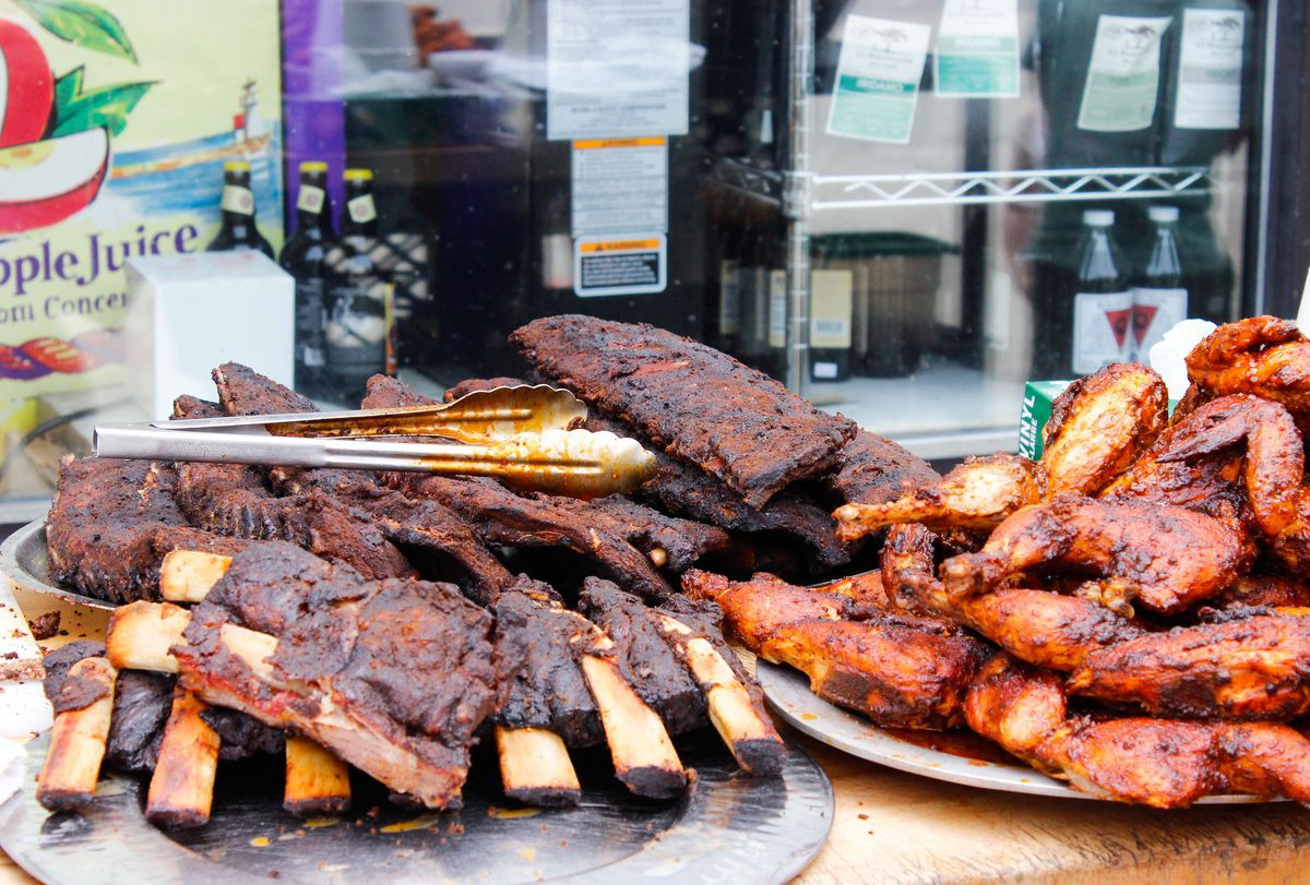 Piles of ribs and wings are set up on a table outdoors in front of a food store window