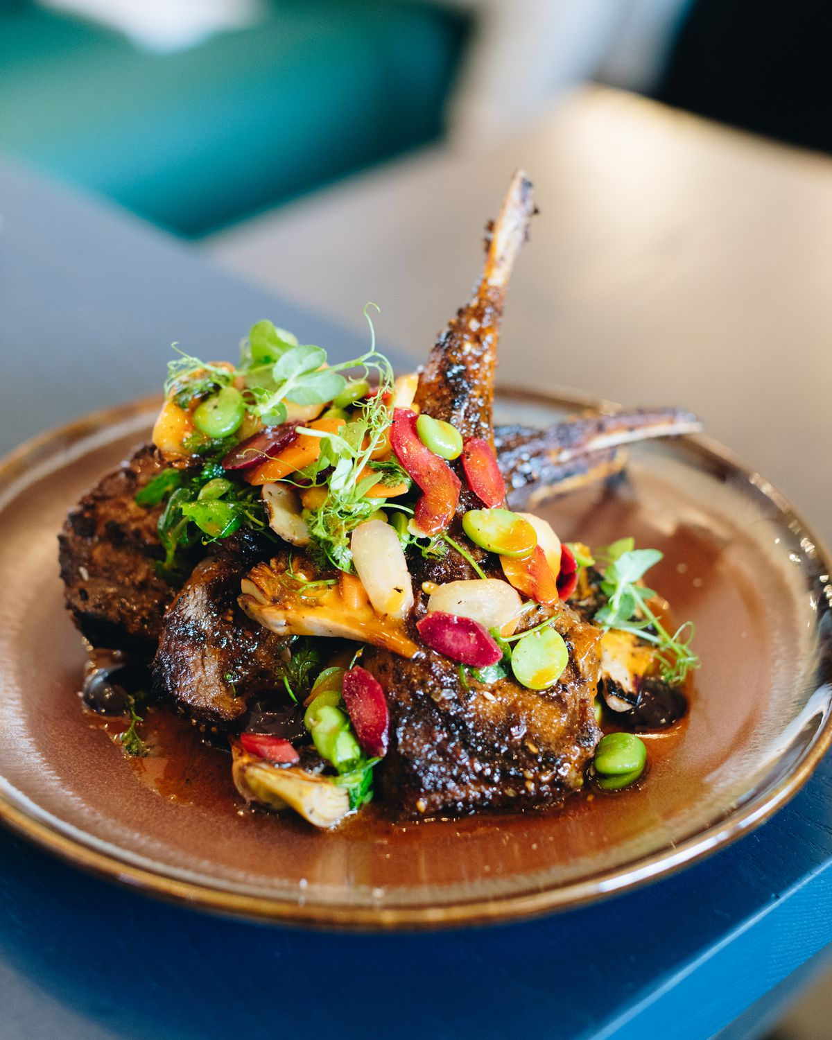 Grilled lamb chops topped with fava beans and various greens, placed on a brown ceramic plate