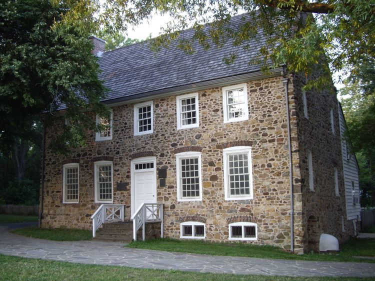 The exterior of the Conference House on Staten Island in New York City. The facade is stone with multiple windows that have white shutters.