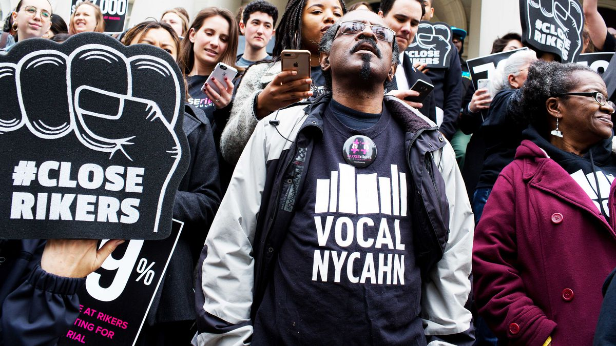 """Criminal justice reform activists hold a rally on the steps of New York's City Hall; One sign reads """"#Close Rikers."""""""