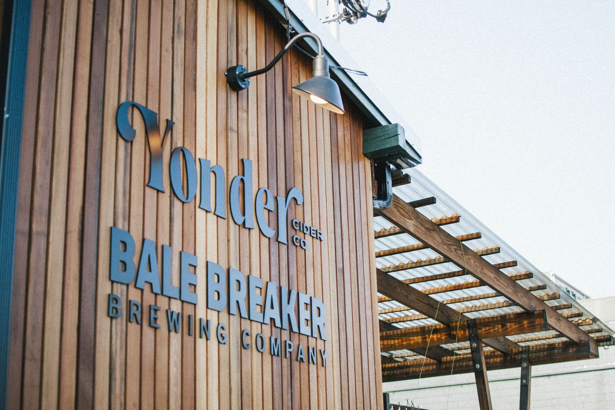 The wood facade of Bale Breaker and Yonder taproom. there's a covered overhang to the right of the main sign displaying the name of each business.
