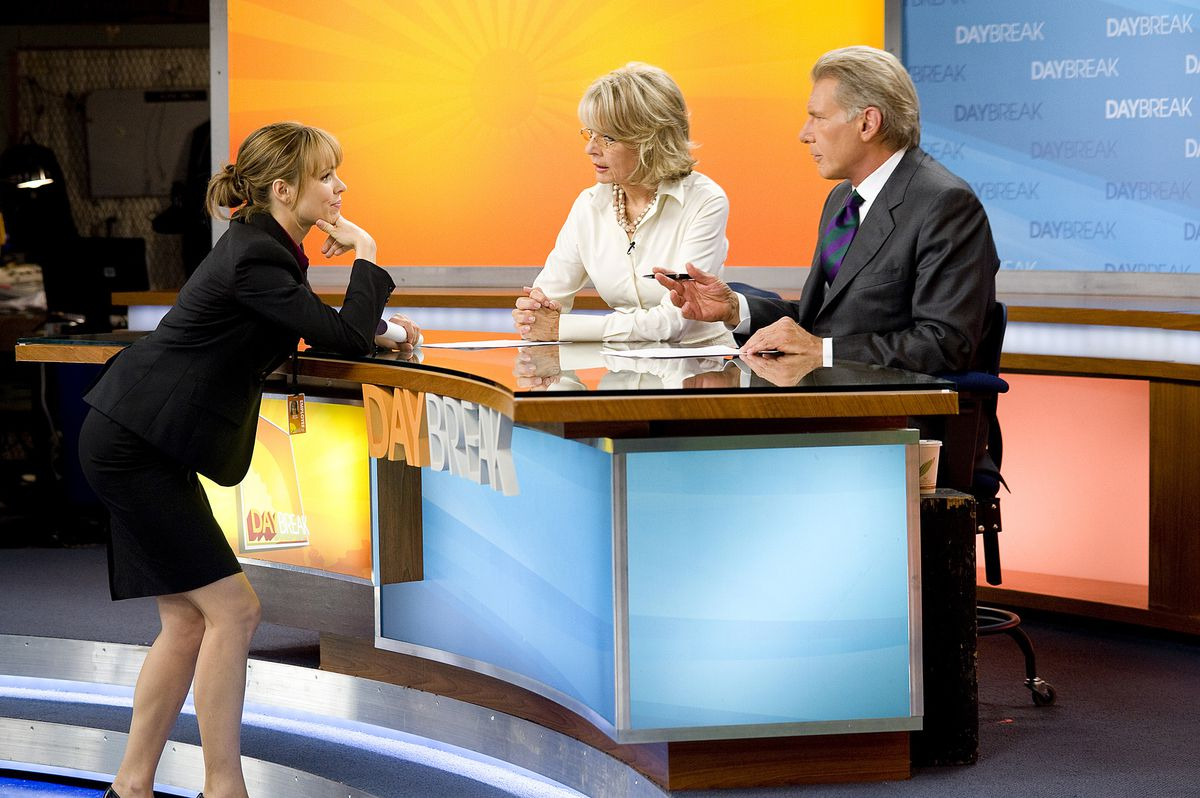 Becky (Rachel McAdams) leans on the morning show desk talking to Colleen (Diane Keaton) and Mike (Harrison Ford)