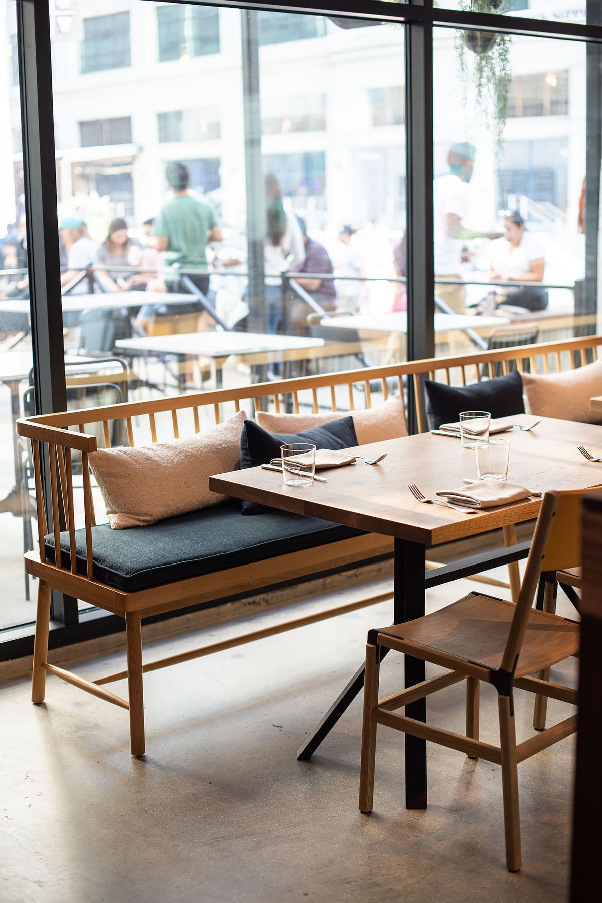 Wooden seating with dark padding at a new restaurant with big windows.