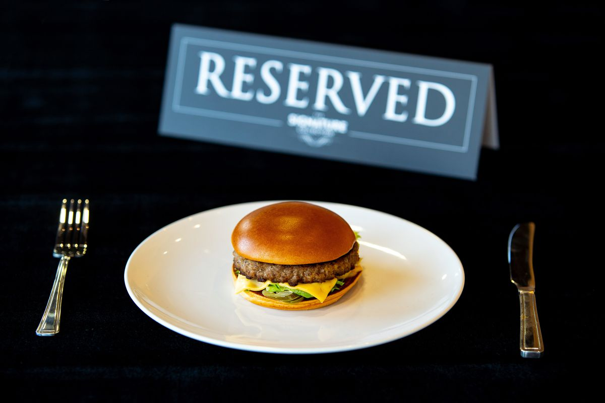 """McDonald's U.K. has taken the signature collection burger off its menu, pictured here with a """"reserved"""" sign and a knife and fork"""